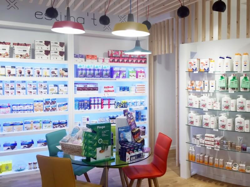 Estanterias y mostradores con mesa y sillas Farmacia Femenia